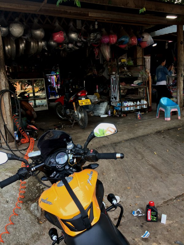 Found a local motorcycle repair shop in Luang Namtha. That's my bottle of Motul 3100 with 600ml of remaining oil from the engine rebuild.