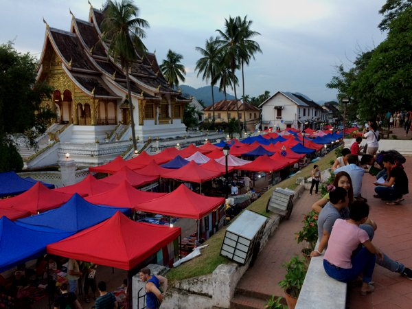 The Luang Prabang night market against the temple Haw Pha Bang in the backdrop.