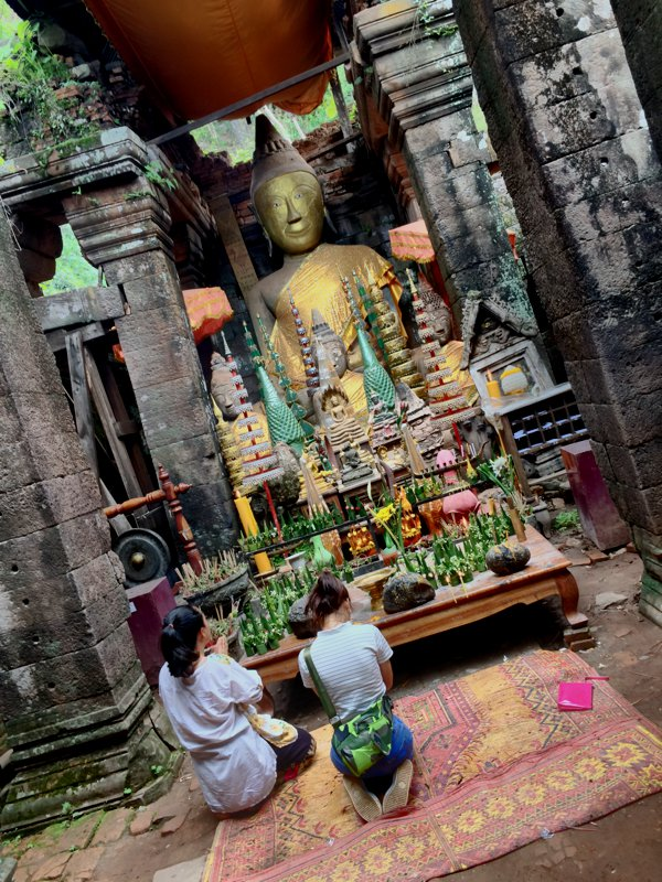 Buddha statue and locals praying inside the temple.